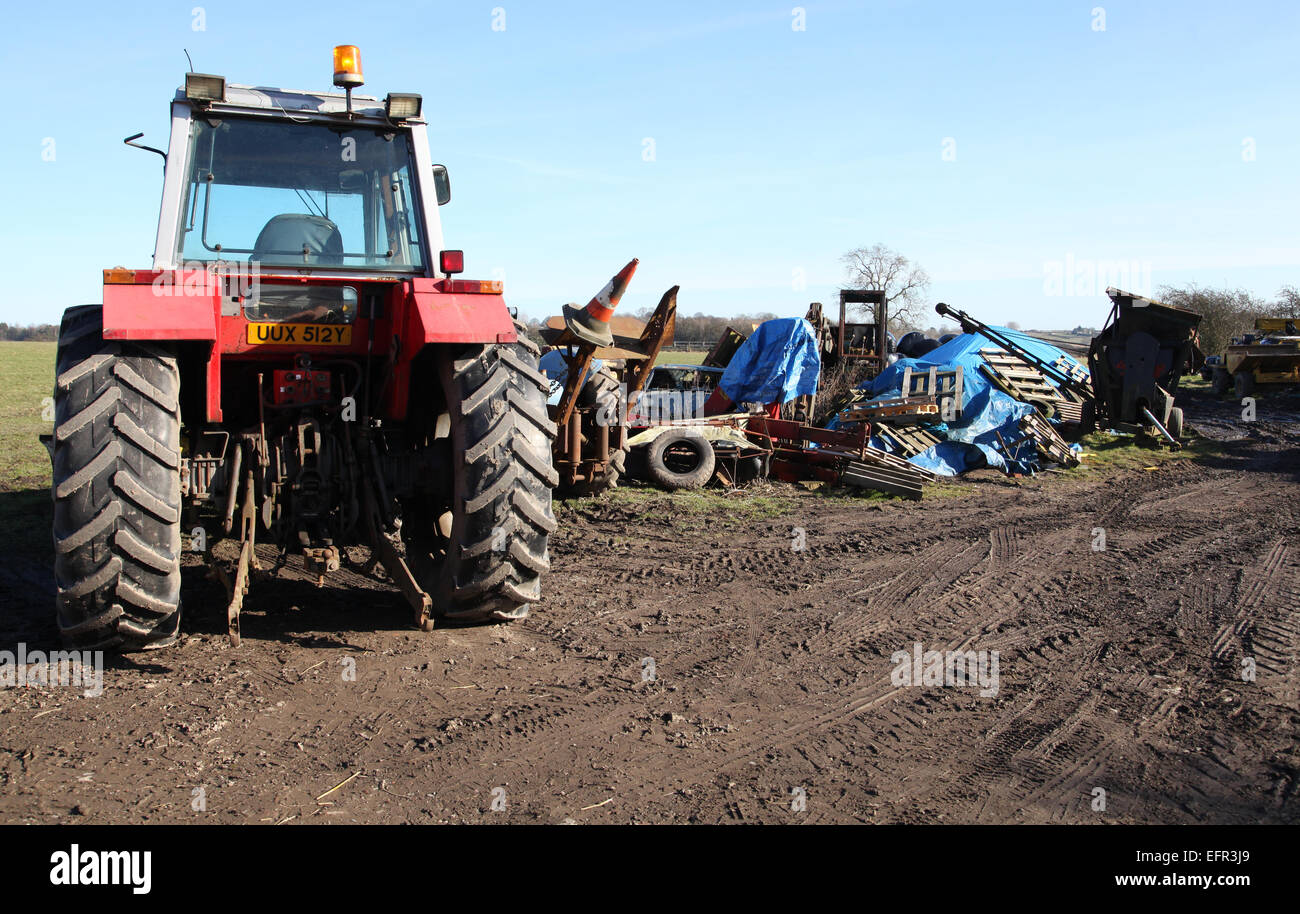 an untidy farmers field with tractor and pile of machinery and junk, UK - Stock Image