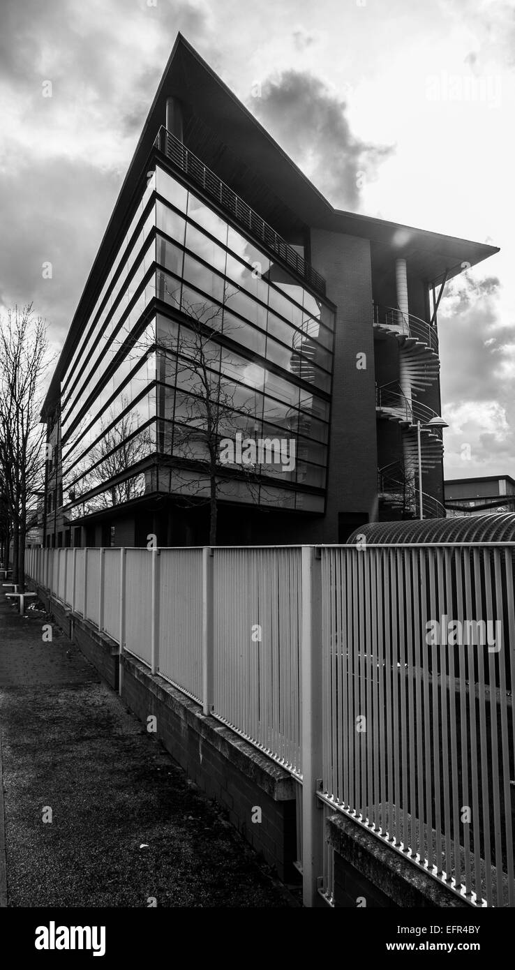 Black and white photo of modern office block with dramatic sky behind.  Building protected by metal fence and fronted - Stock Image