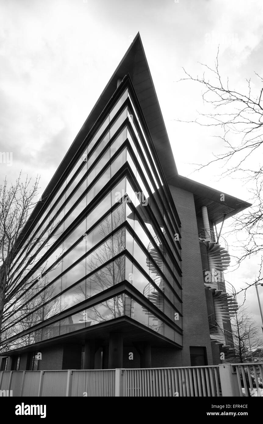 Black and white photo of modern office block with dramatic sky behind.  Building protected by metal fence - Stock Image