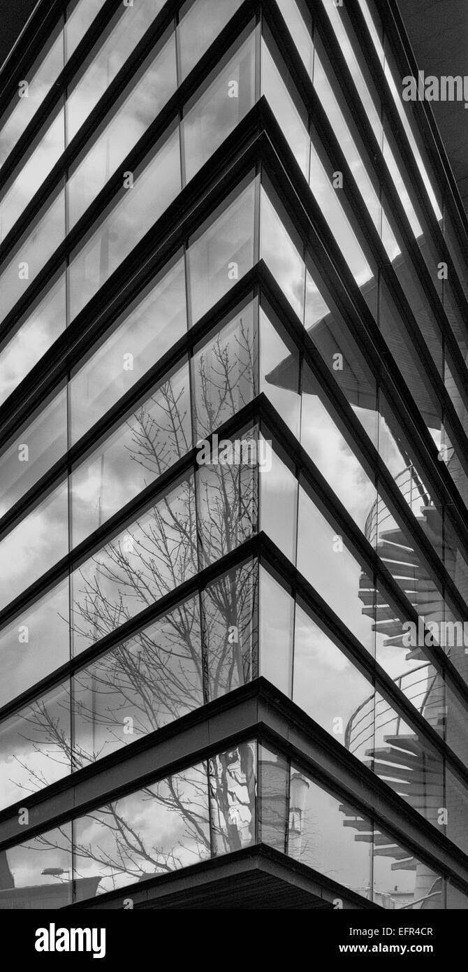 Black and white photo showing sharp corner of glass facade with reflections of clouds, trees and spiral staircase - Stock Image