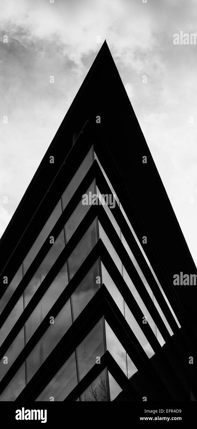 Black and white photo looking up at pointed glass facade with roof overhang and clouds beyone - Stock Image
