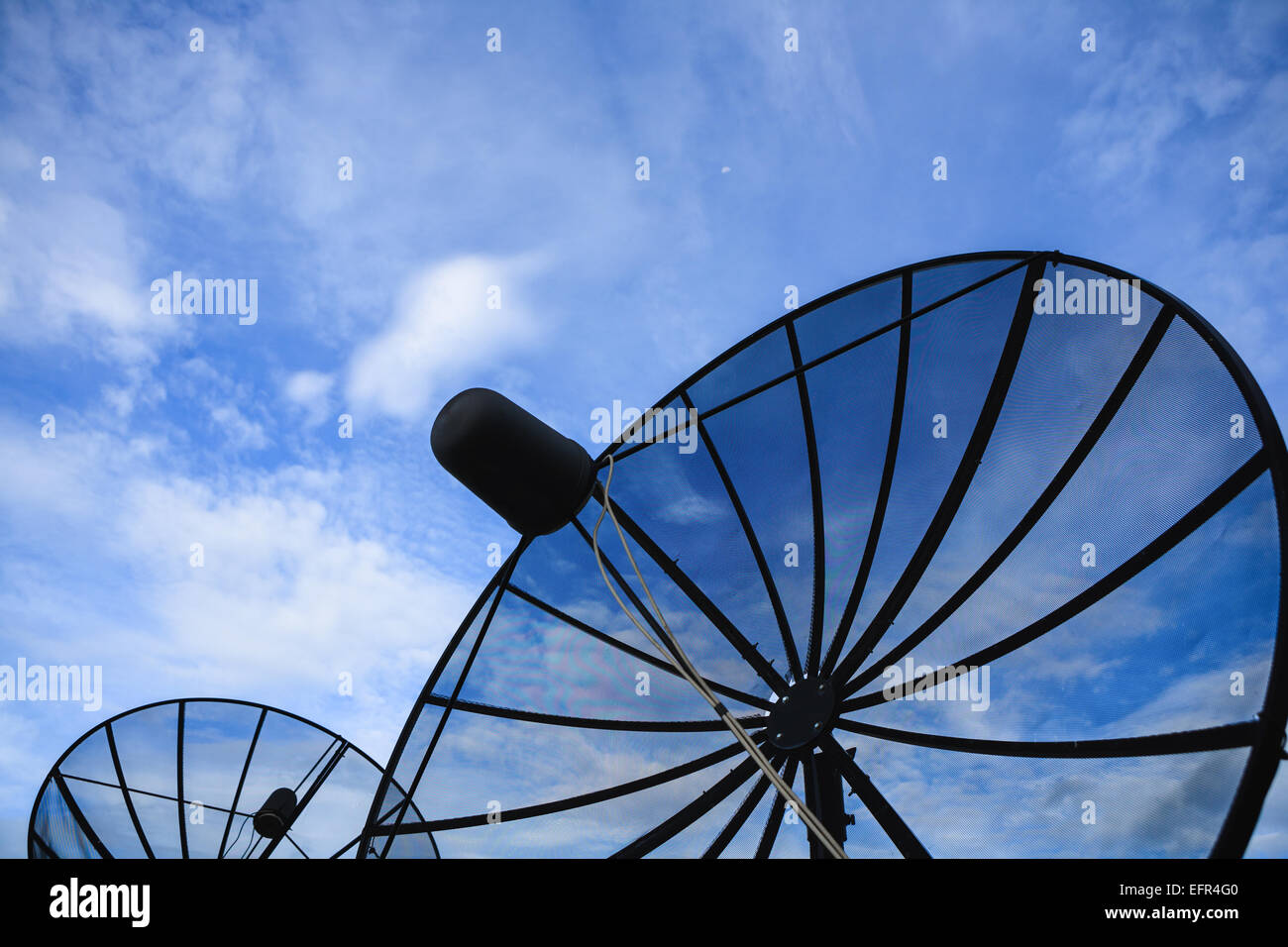 Double black Satellite dish against blue cloudy sky in early morning - Stock Image