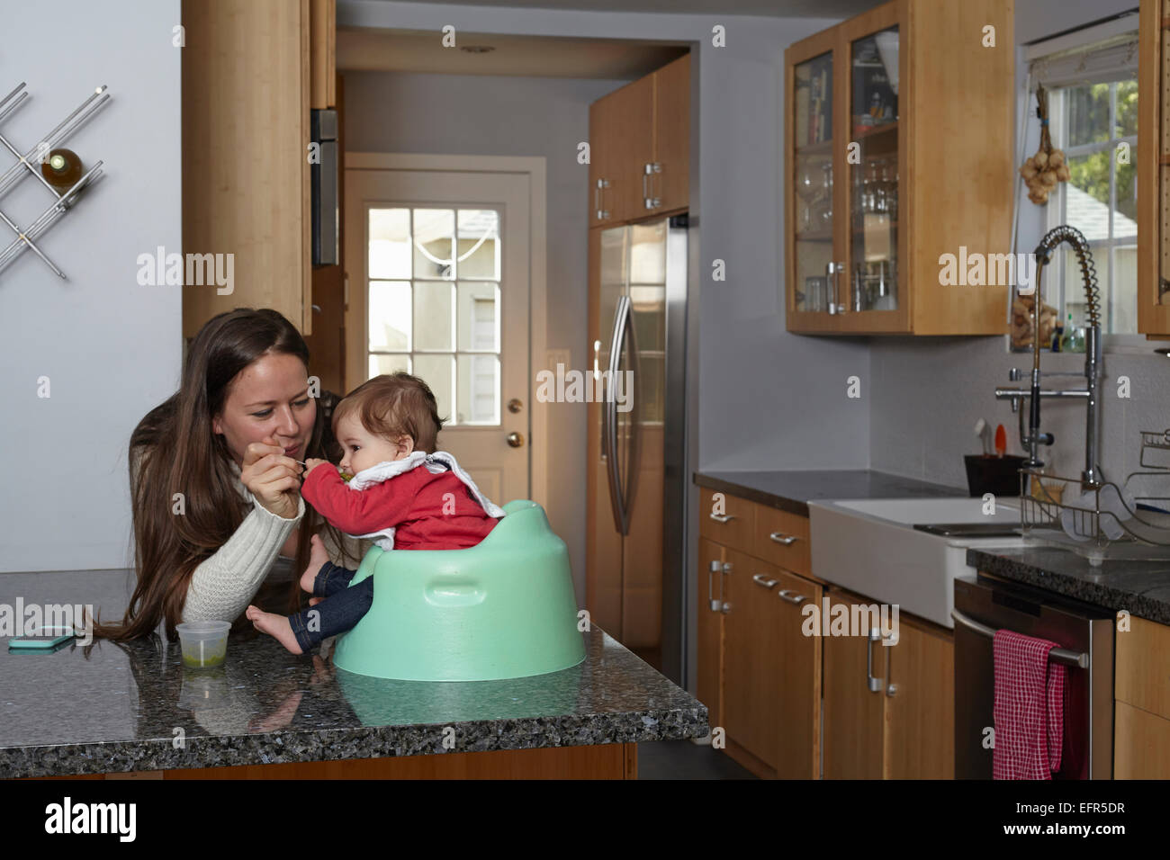 Mother feeding baby girl on kitchen counter - Stock Image