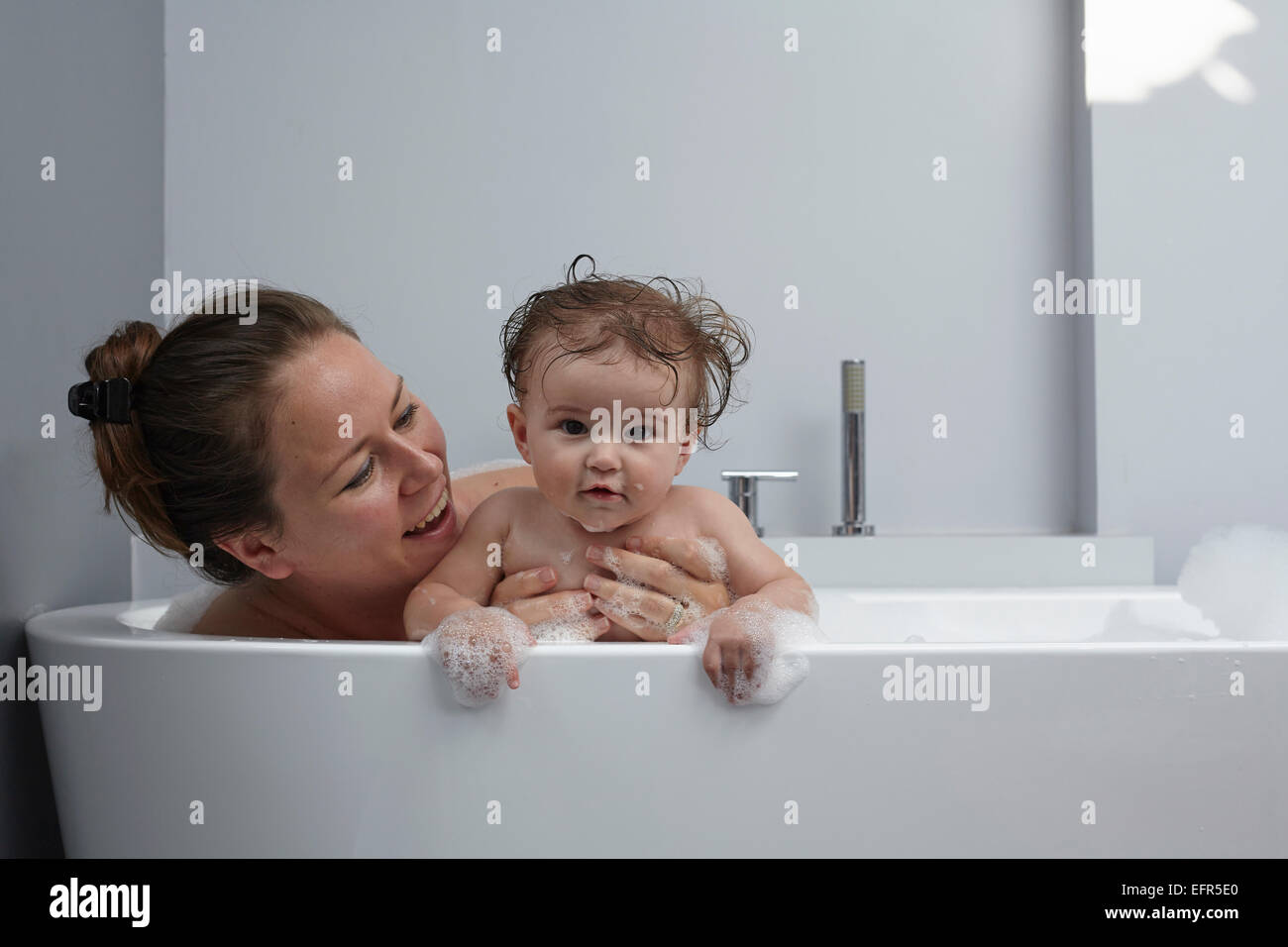 Mother and baby girl in bathtub - Stock Image