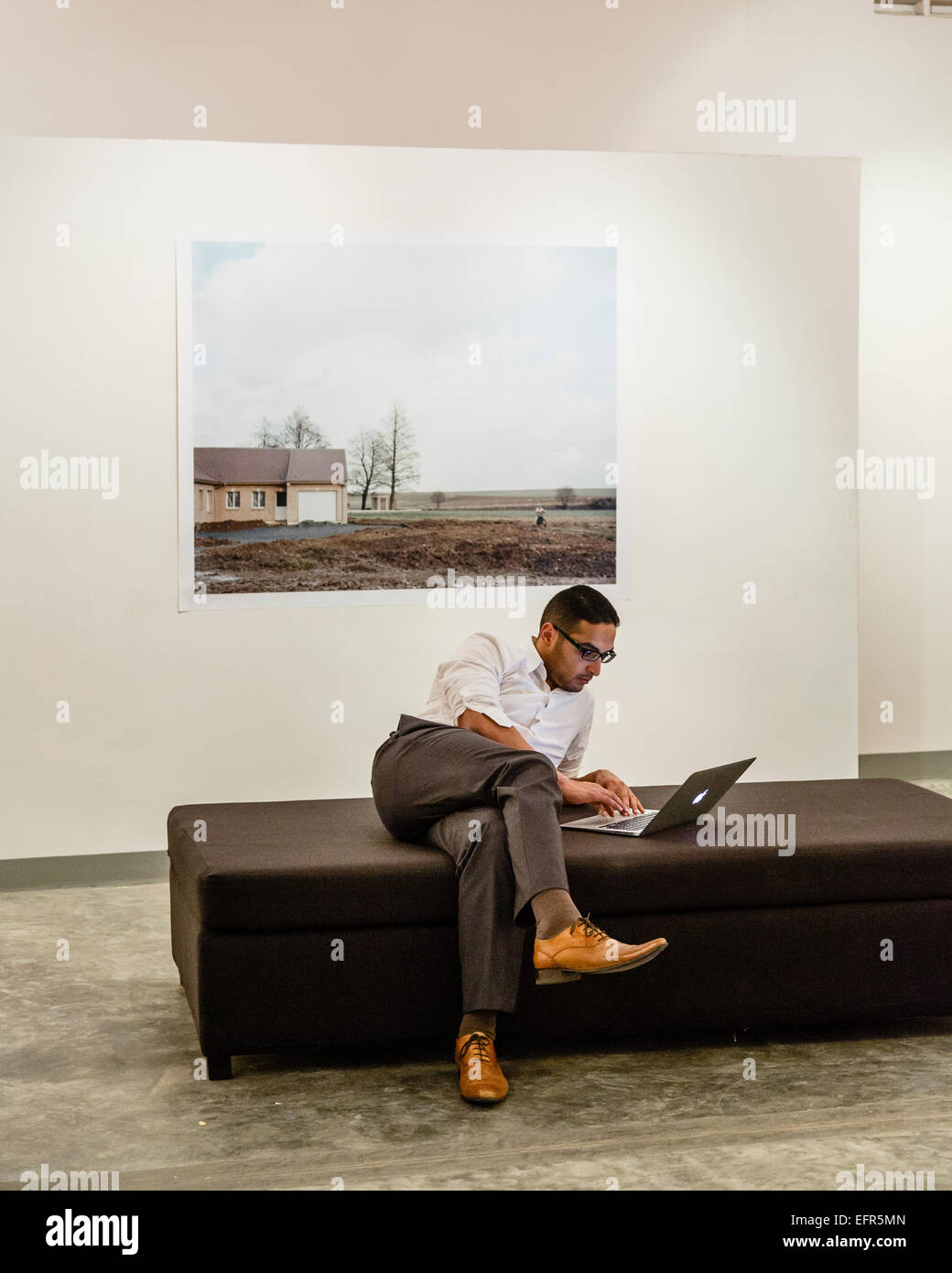 Young man sitting with a laptop computer at an art gallery, Phnom Penh, Cambodia. - Stock Image
