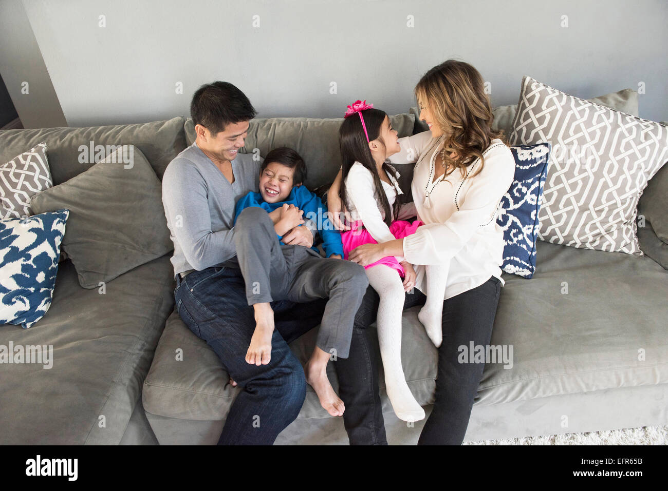 Mature couple and two children sitting on living room sofa - Stock Image