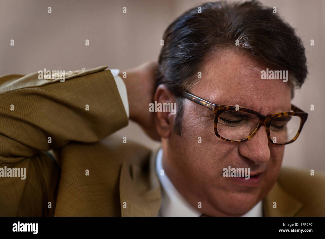 Close up of mature businessman with eyes closed and hand on head - Stock Image