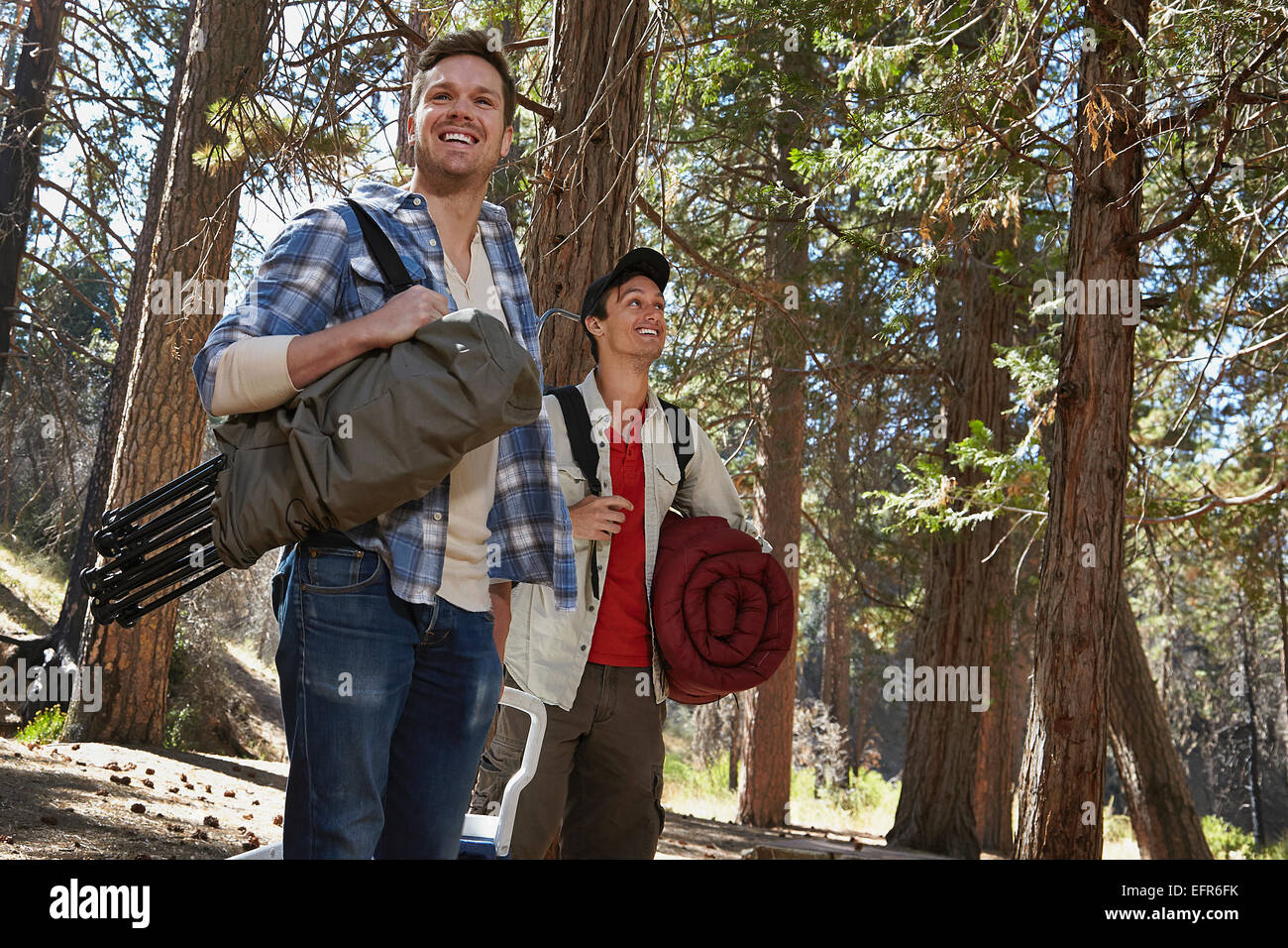 Two young men walking in forest with camping equipment, Los Angeles, California, USA - Stock Image