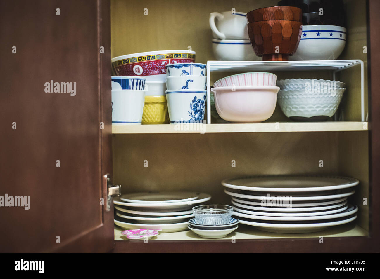Open cupboard displaying crockery - Stock Image