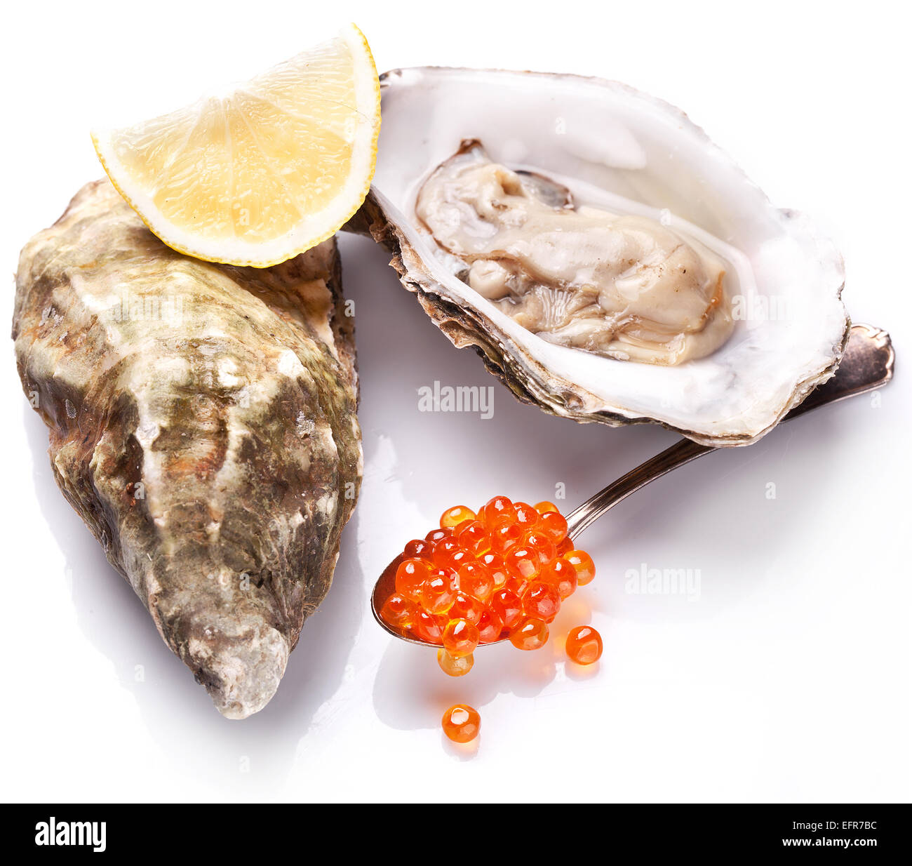 Raw oyster,lemon and red caviar isolated on a white background. - Stock Image