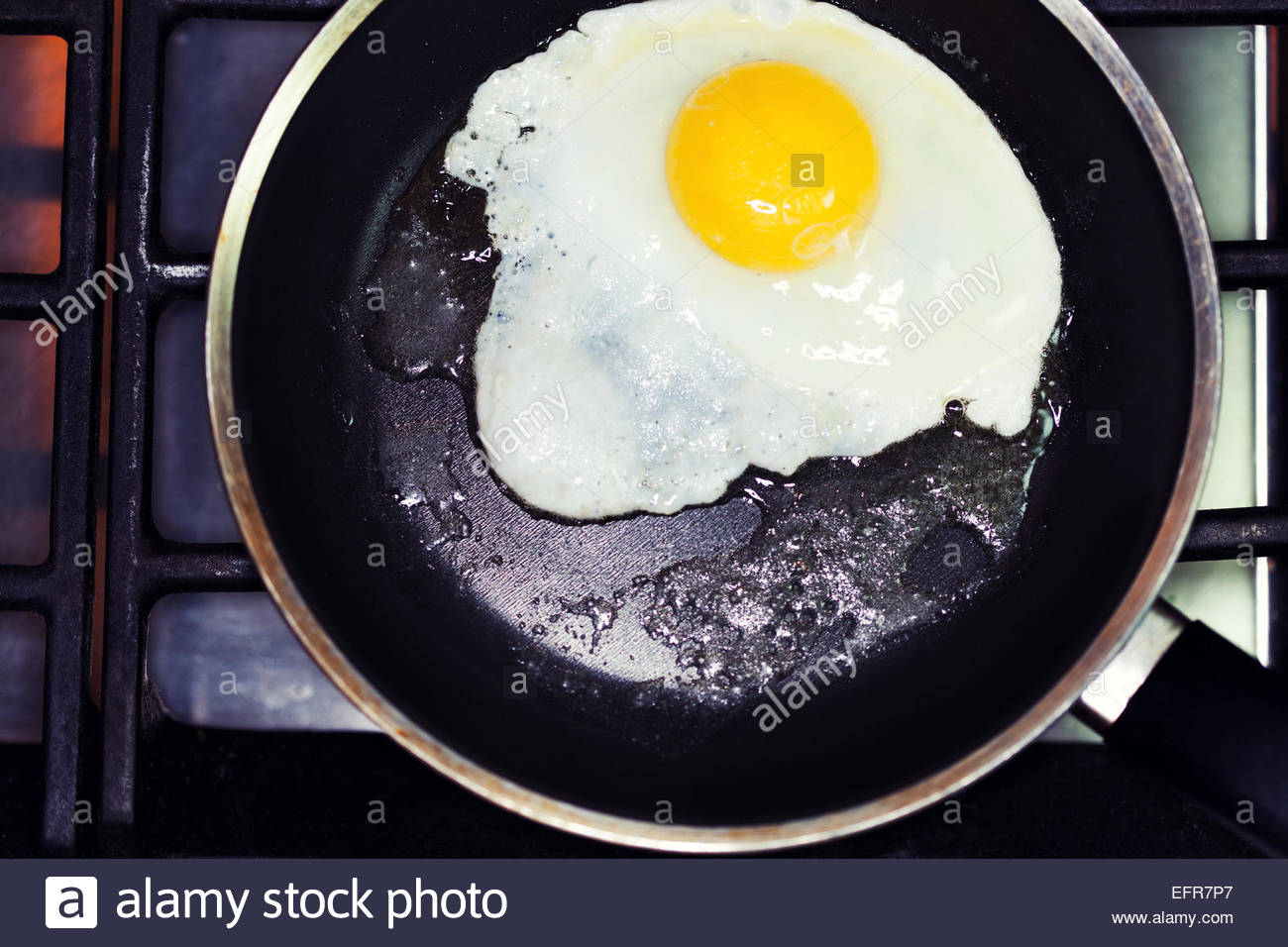 Overhead view of fried egg in frying pan - Stock Image