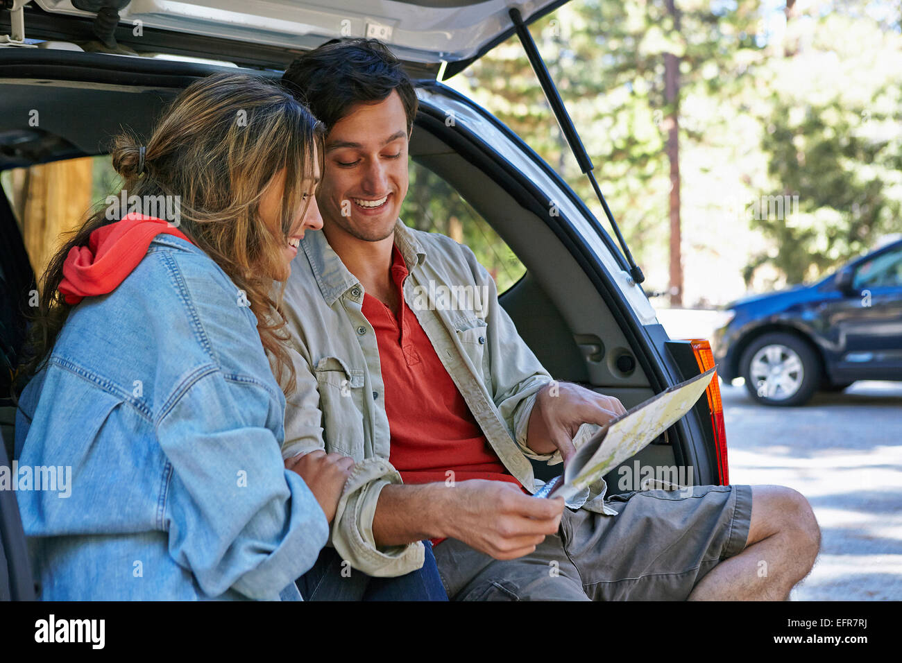 Young couple sitting on car boot looking at map, Los Angeles, California, USA - Stock Image