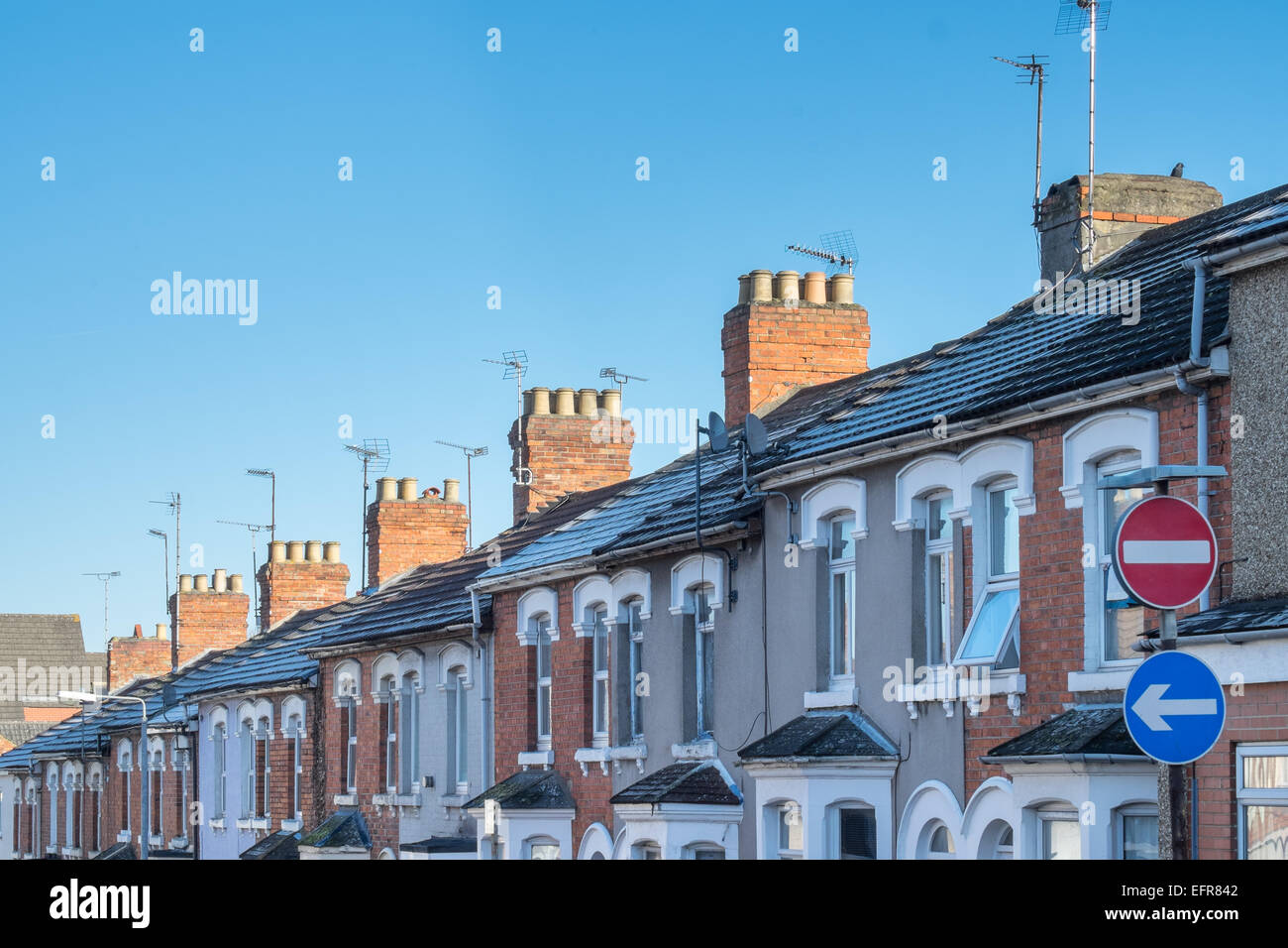 The frontages, rooftops, chimneys & TV aerials of  typical Victorian, terraced homes in a UK, Suburban street - Stock Image