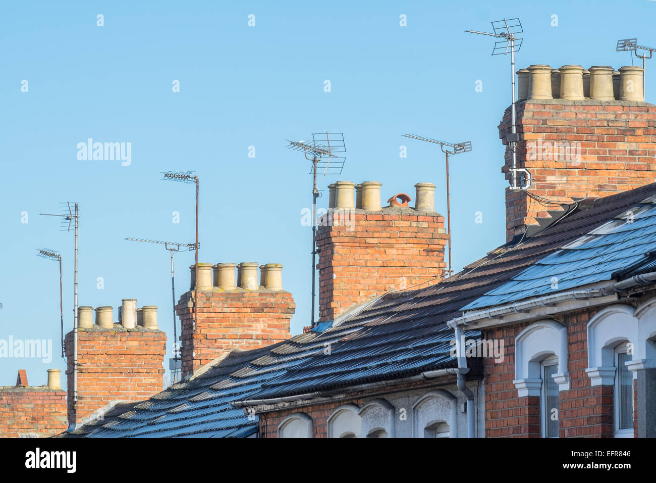 The rooftops, chimneys & TV aerials of  typical Victorian, terraced homes in a UK, Suburban street on a clear - Stock Image