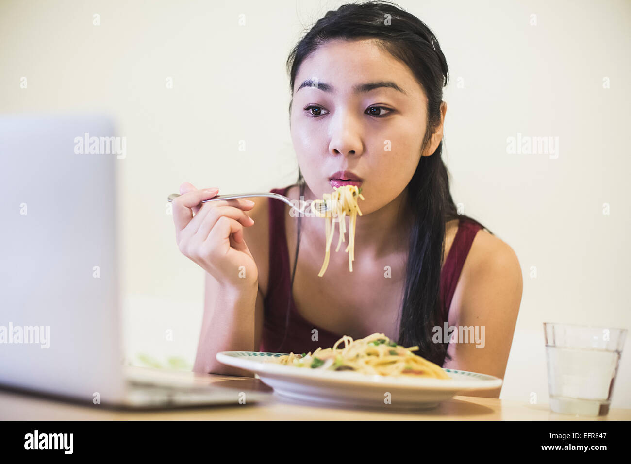 Young woman at table eating plate of noodles - Stock Image
