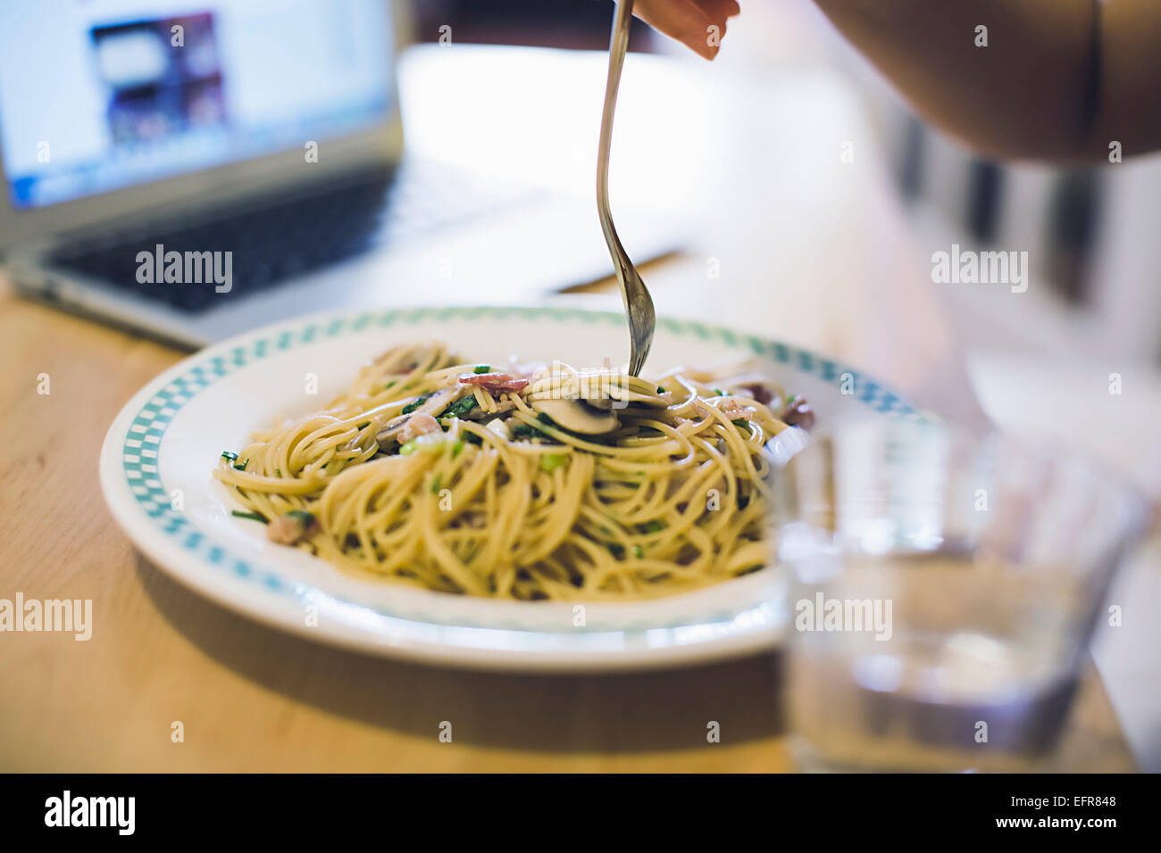 Young woman at table eating plate of noodles, focus on food - Stock Image