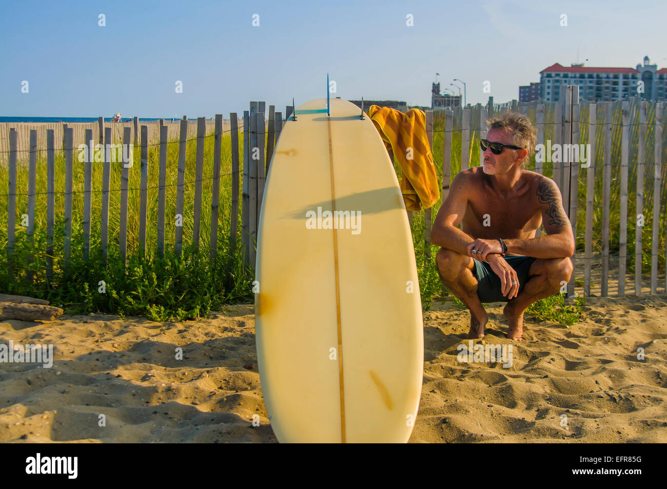Mature male surfer crouching with surfboard at beach Stock Photo