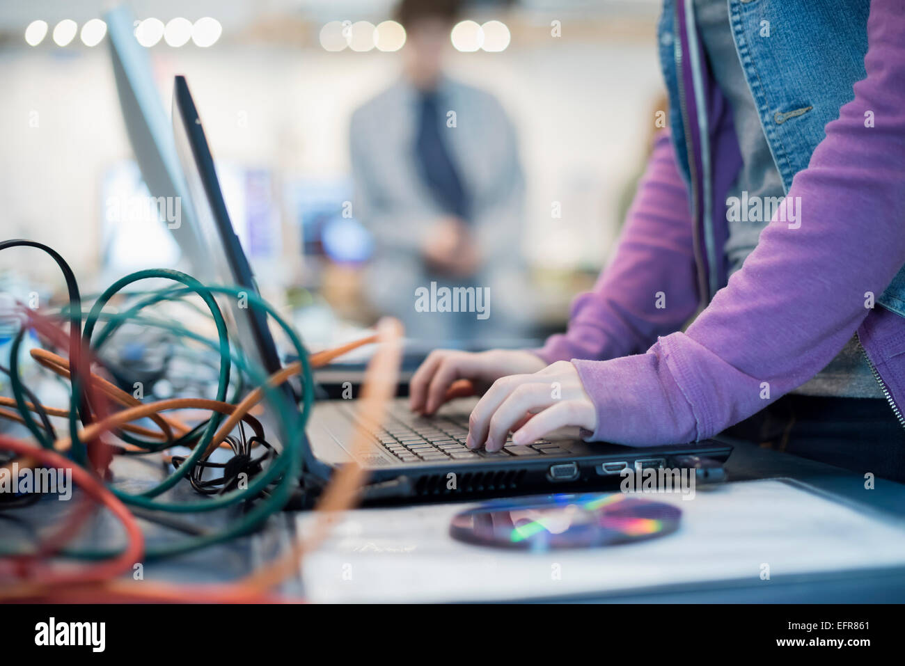 A person using a laptop computer. Disc and wires on the counter. Repair shop. Stock Photo