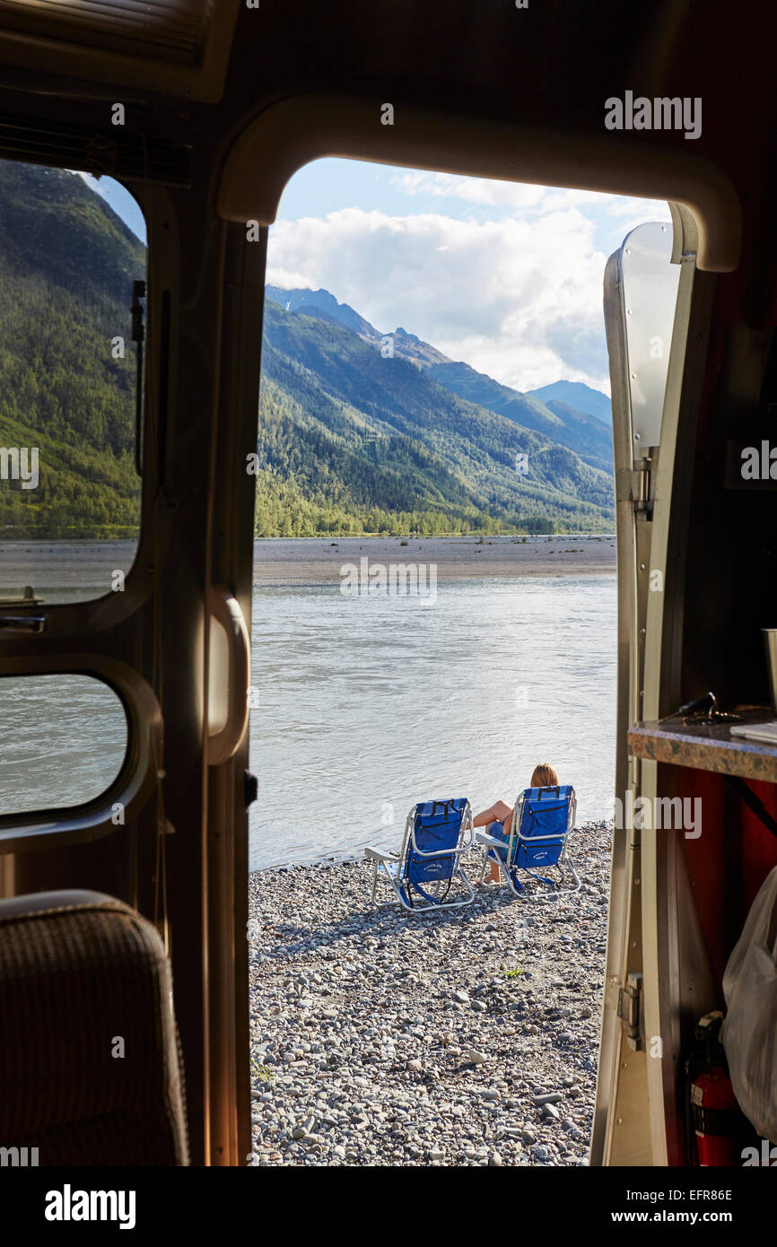 View from camper van doorway of mid adult woman sitting by lake, Palmer, Alaska, USA - Stock Image