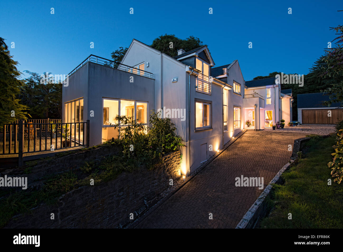 An aspirational, detached, self build home with all lights ablaze.Just after sunset on a clear Evening. UK - Stock Image