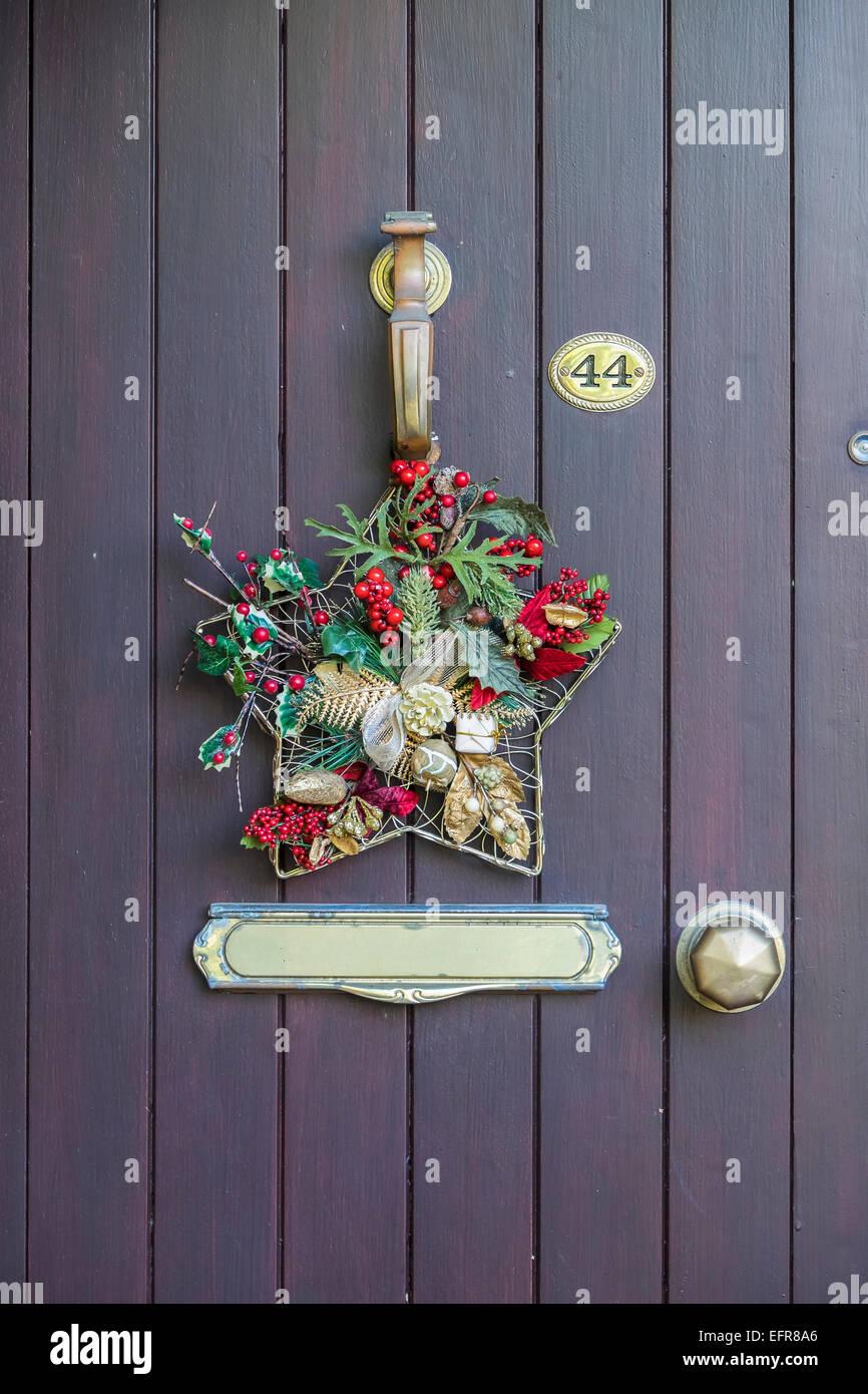 Christmas Decorative Wreath Hung On Front Door Knocker Stock Photo Alamy