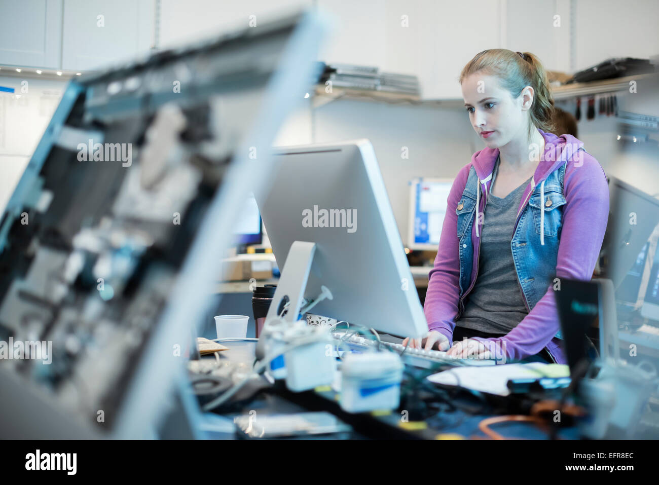 Computer Repair Shop. A woman standing typing at a keyboard. - Stock Image