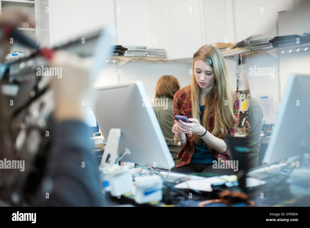 Computer Repair Shop. A woman using a smart phone.  People working on computer repairs. - Stock Image