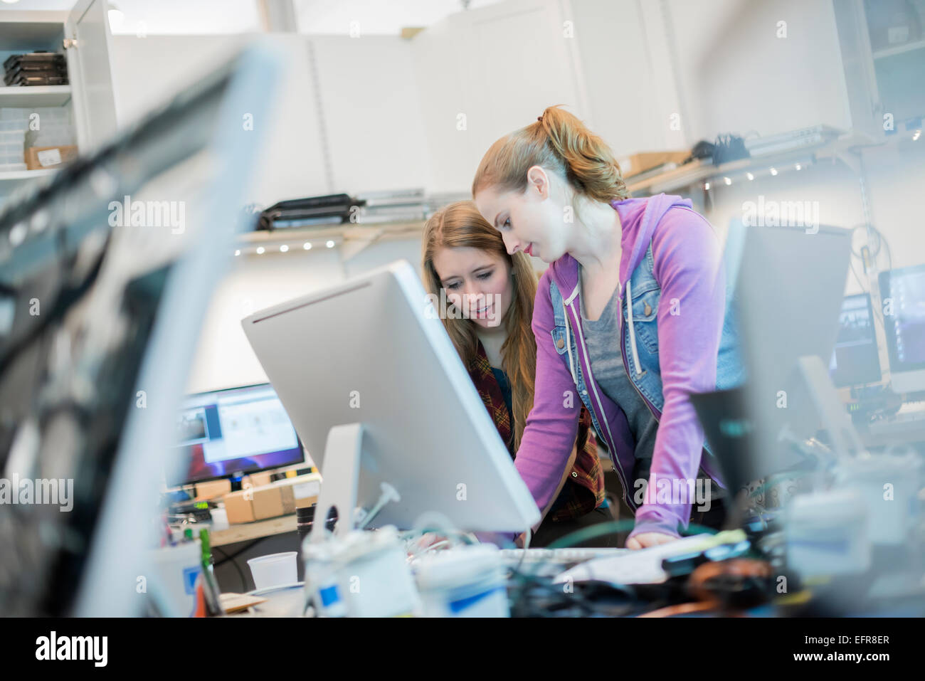 Computer Repair Shop. Two women working together leaning ou a counter. - Stock Image