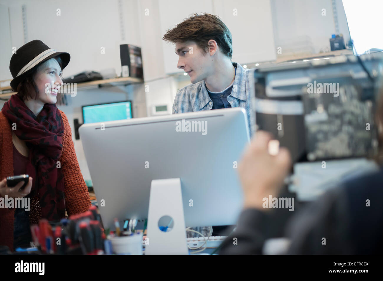 Computer Repair Shop. A man and woman talking over a computer. - Stock Image
