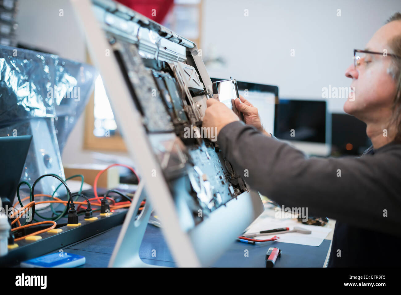 Computer Repair Shop. A man with a computer monitor, taking it apart to mend it. - Stock Image