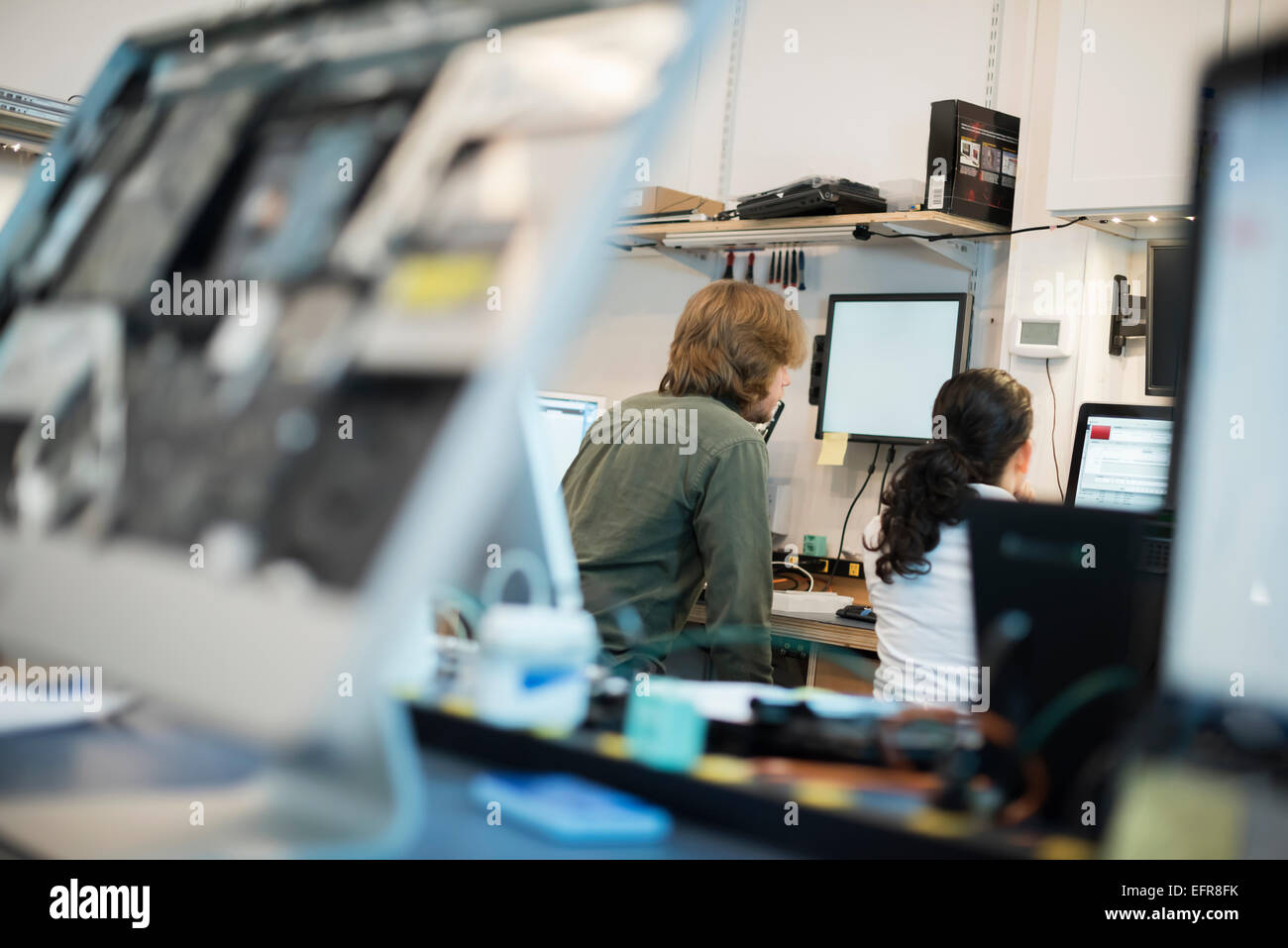 Computer Repair Shop. Two people seated using screens, and computer monitors in various stages of repair. - Stock Image