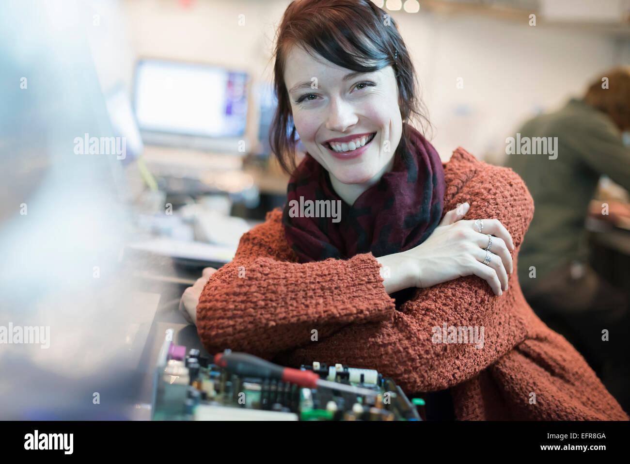 Computer Repair Shop. A woman smiling and leaning on a workshopcounter. - Stock Image