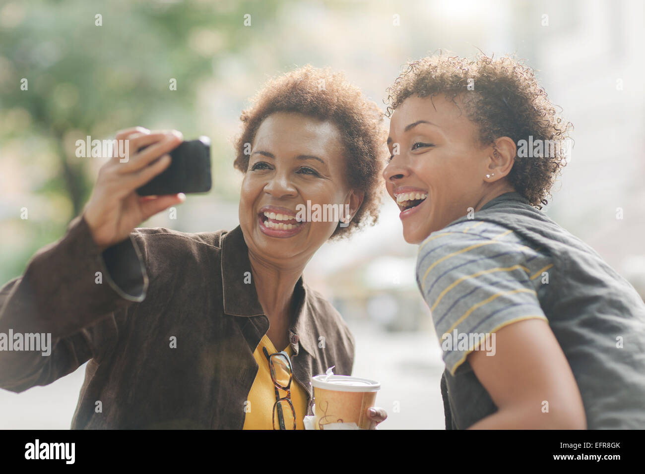 Two mature female friends taking smartphone selfie on street - Stock Image