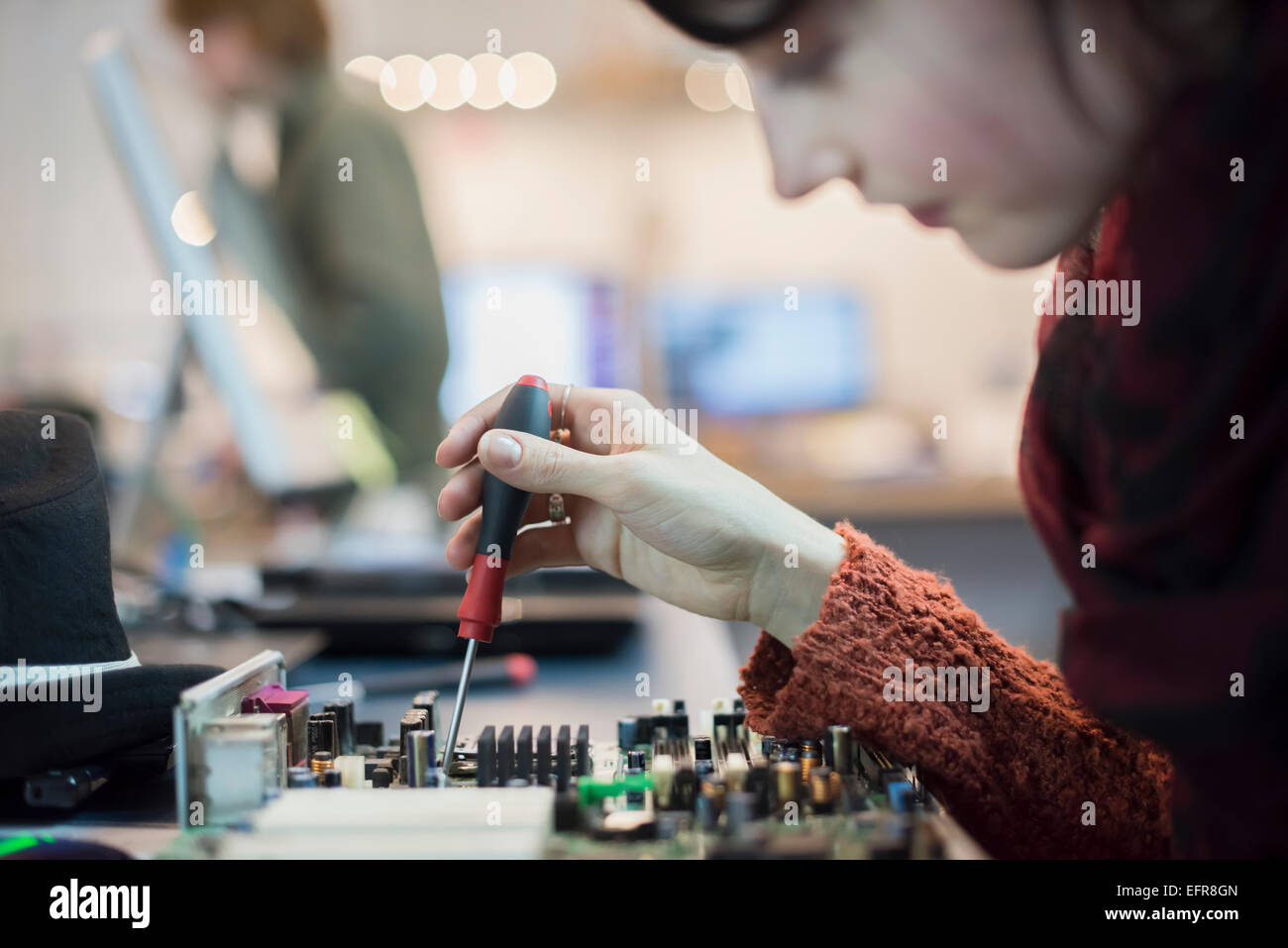 Computer Repair Shop. A woman using an electronic screwdriver tool on a computer circuit board. - Stock Image