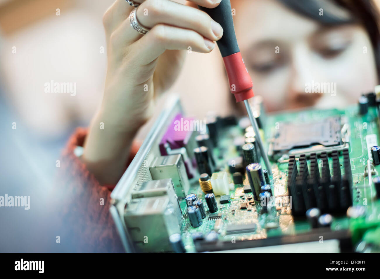 A woman using an electronic screwdriver on a computer circuitboard. - Stock Image
