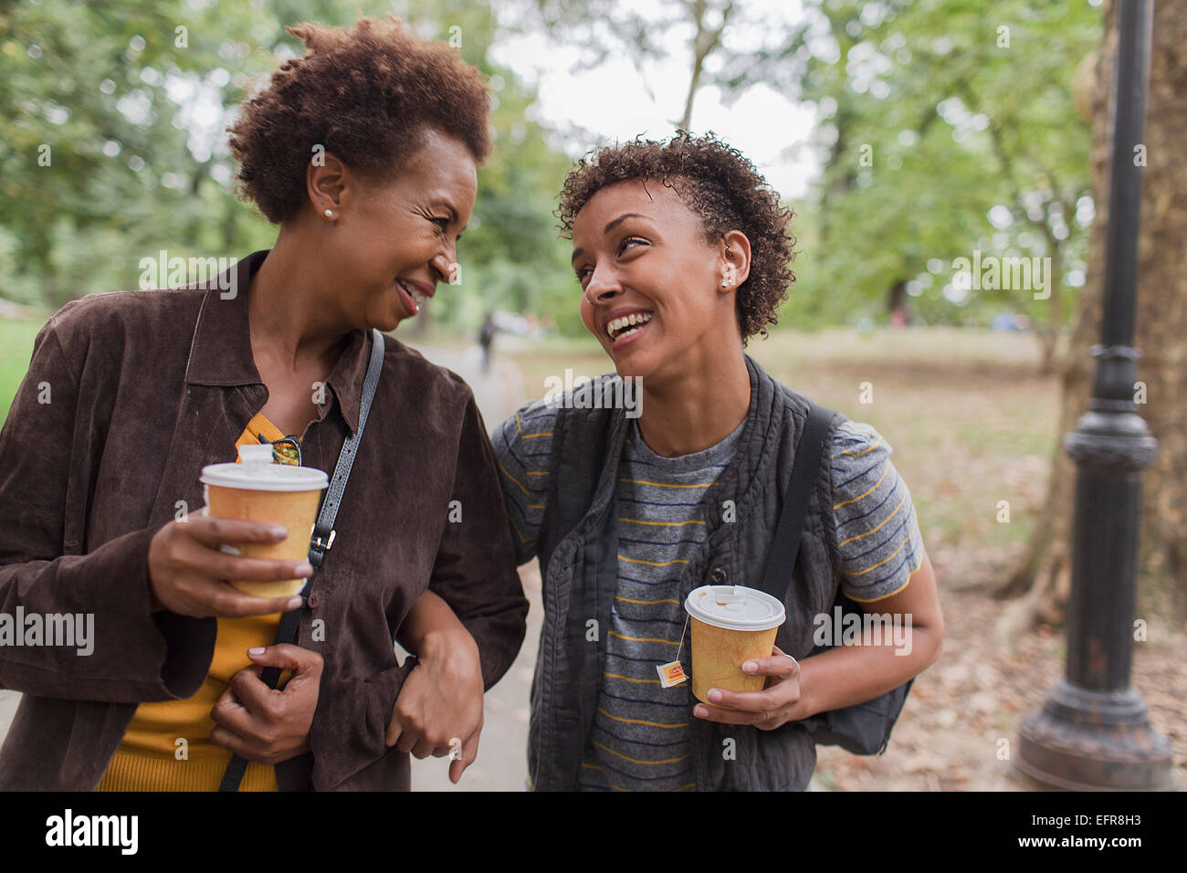 Two mature female friends drinking takeaway coffee whilst strolling  in park - Stock Image