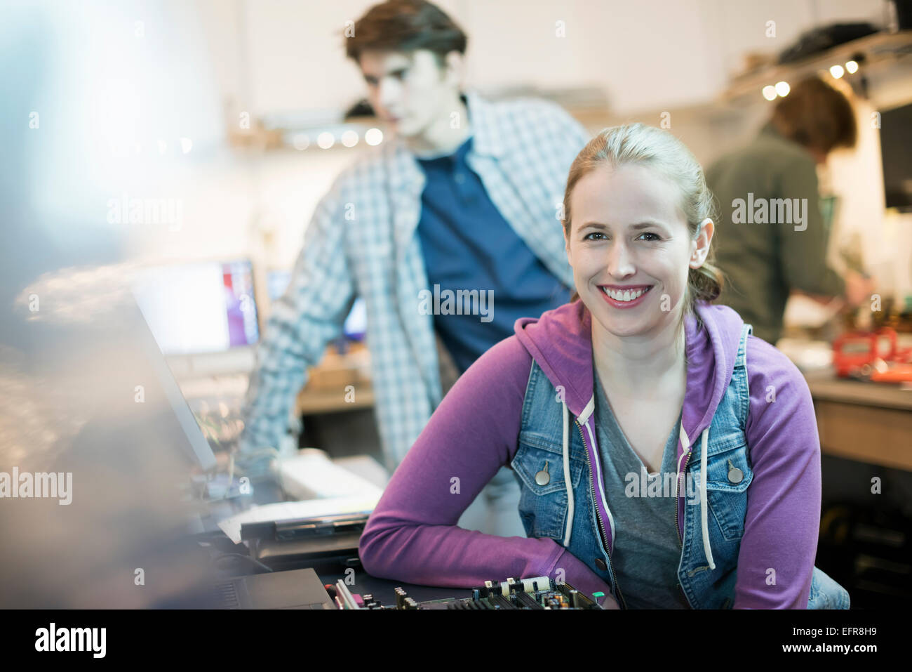 A young woman and man, staff in a computer repair shop. - Stock Image