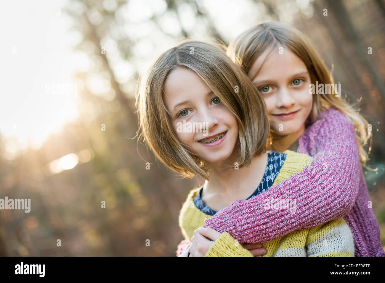Two smiling girls in a forest, hugging each other. - Stock Image