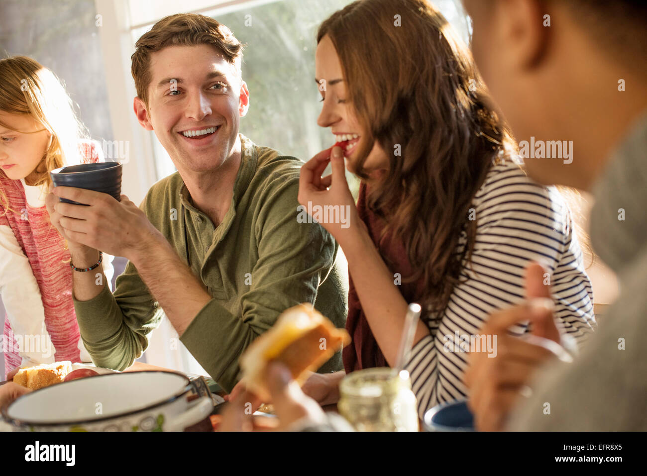 A group of people sitting at a table, smiling, eating, drinking and chatting. - Stock Image
