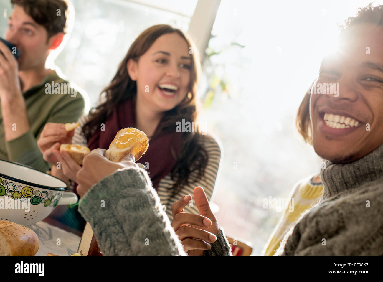 Three people sitting at a table, smiling, eating, drinking and chatting. - Stock Image