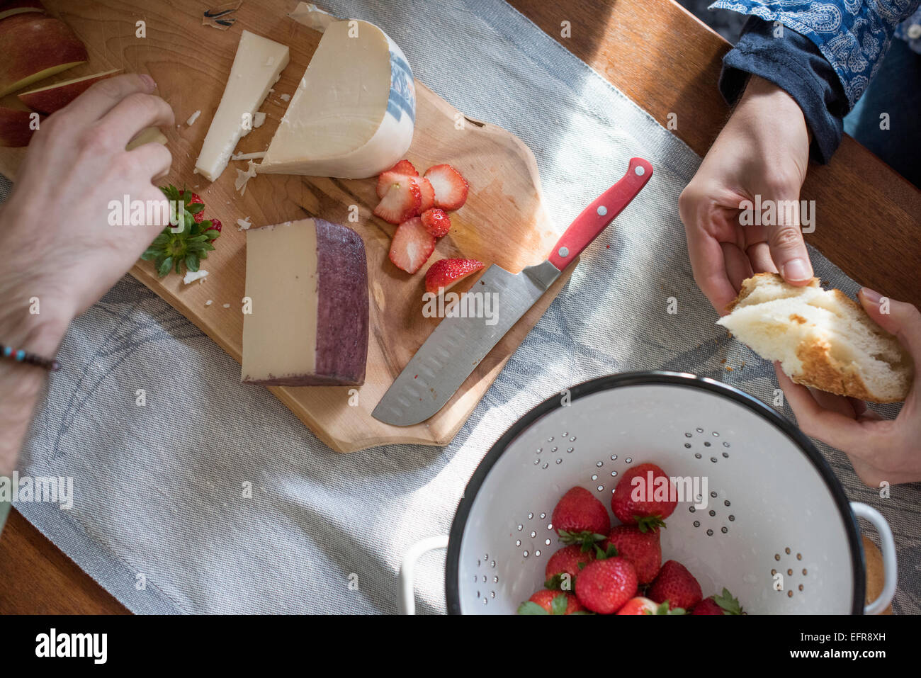 Man and woman sitting at a table with a wooden chopping board with a selection of cheeses, strawberries and bread. - Stock Image