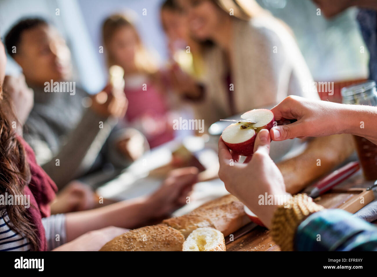 A group of people sitting at a table, eating and chatting. A woman slicing an apple. - Stock Image