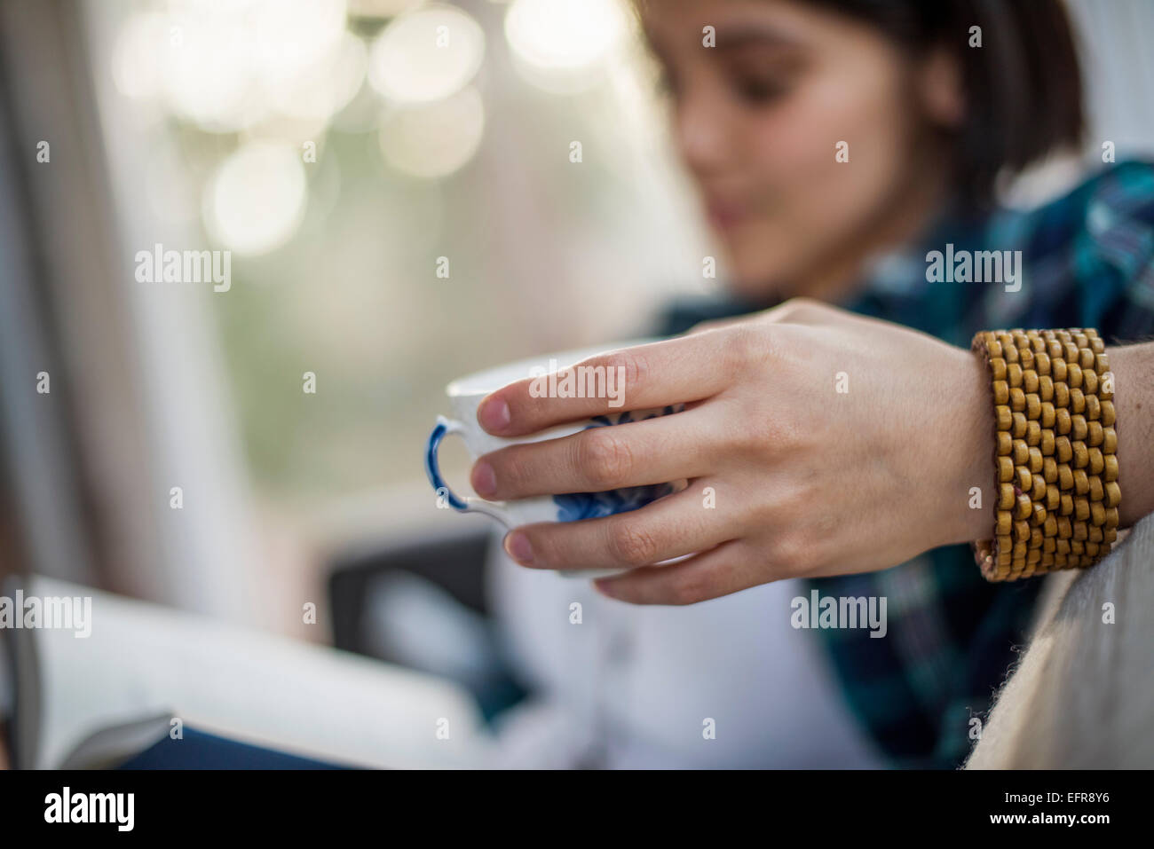 Close up of a woman's hand holding a tea cup, wearing a bracelet. Stock Photo