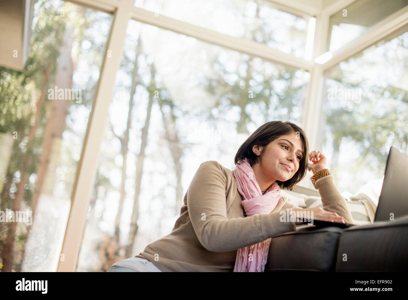 Woman sitting on the floor in front of a sofa looking at her laptop. - Stock Image