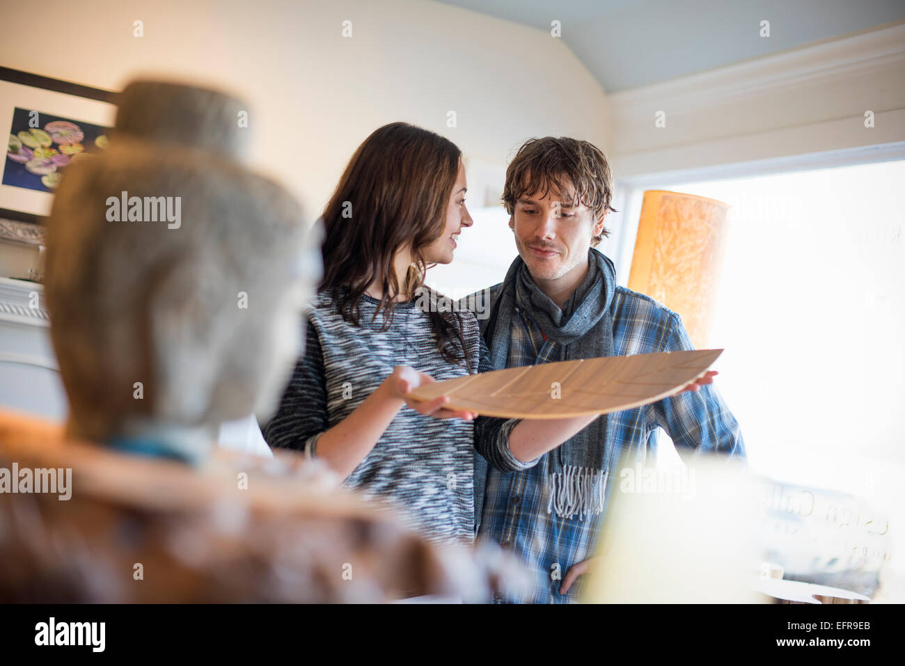 Smiling couple standing in a living room, woman holding a wooden tray. - Stock Image