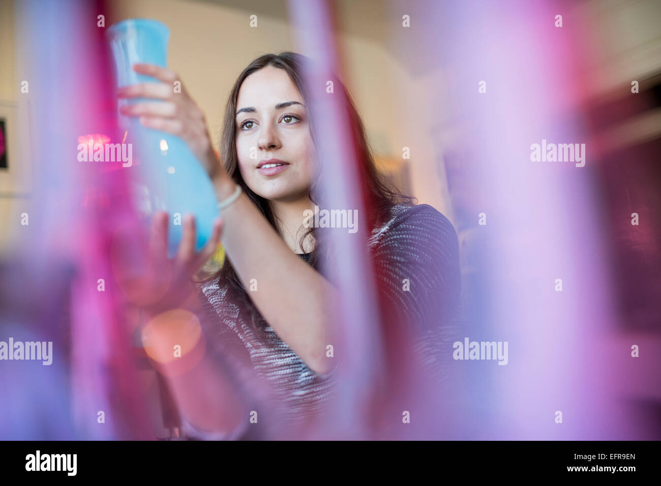 Woman holding a blue glass vase. Red and pink vases in the foreground. - Stock Image