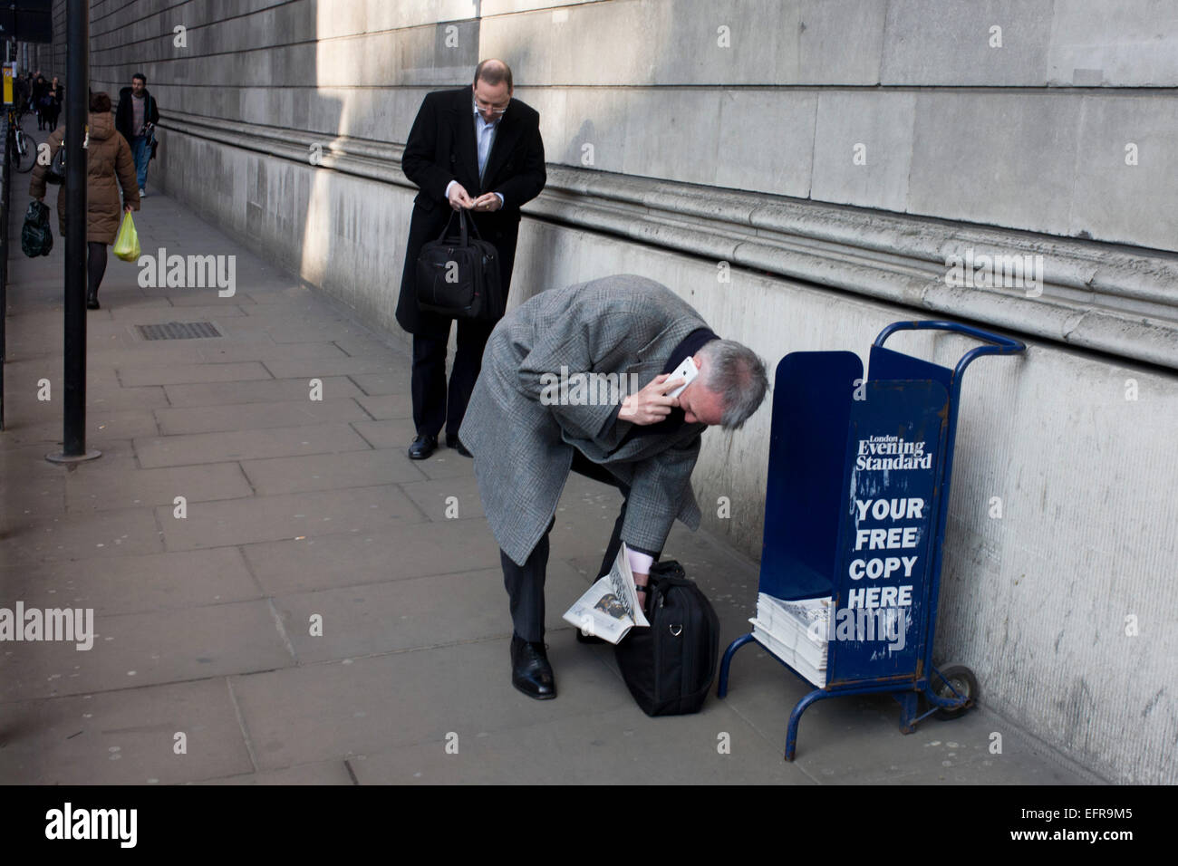 While holding a conversation on his smartphone, a stooping gent struggles to slide a free copy of the Evening Standard - Stock Image