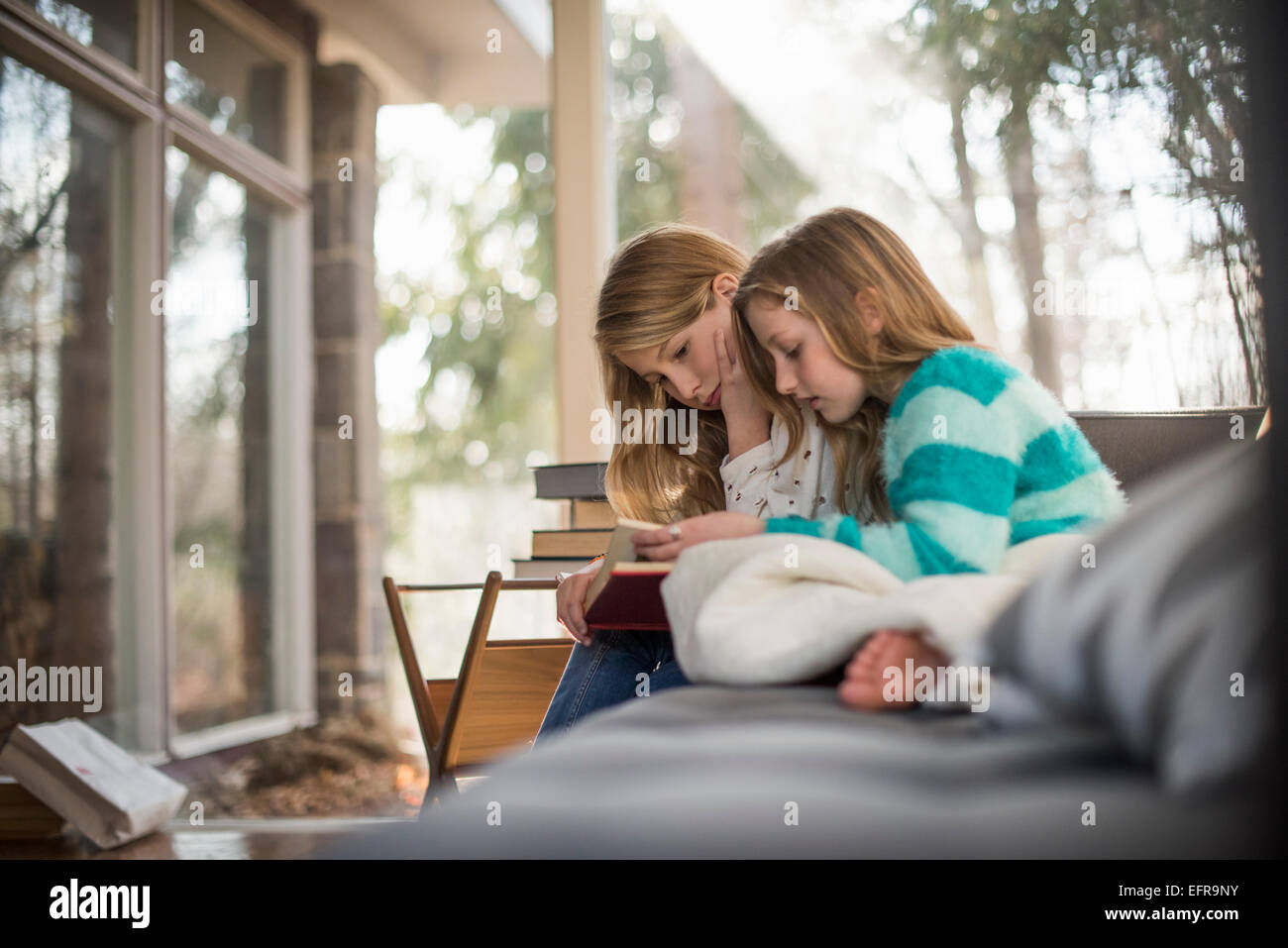 Two girls sitting on a sofa, reading a book. - Stock Image