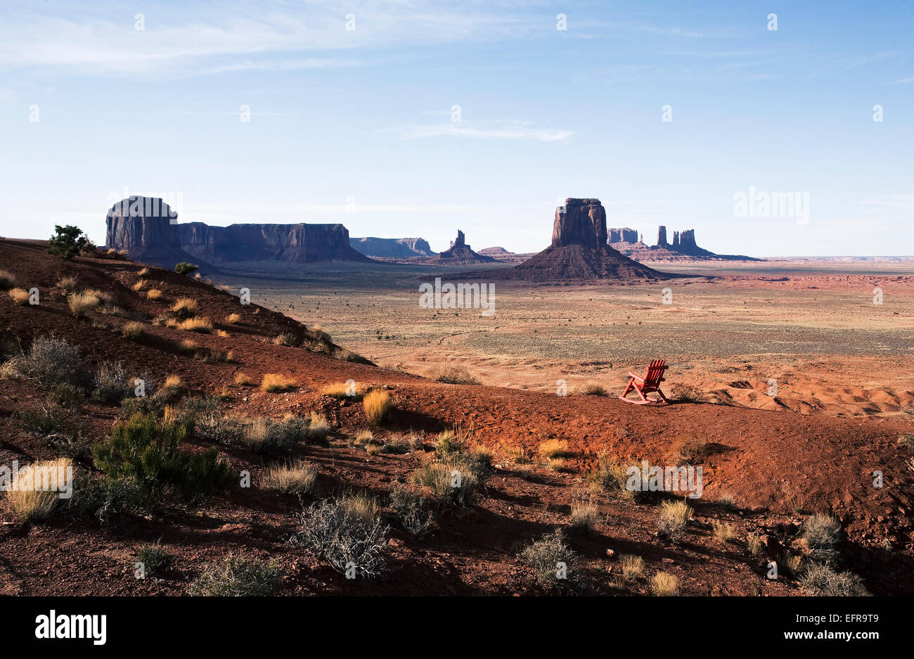 The landscape and eroded sandstone buttes and structure of Monument Valley. A single wooden chair. - Stock Image