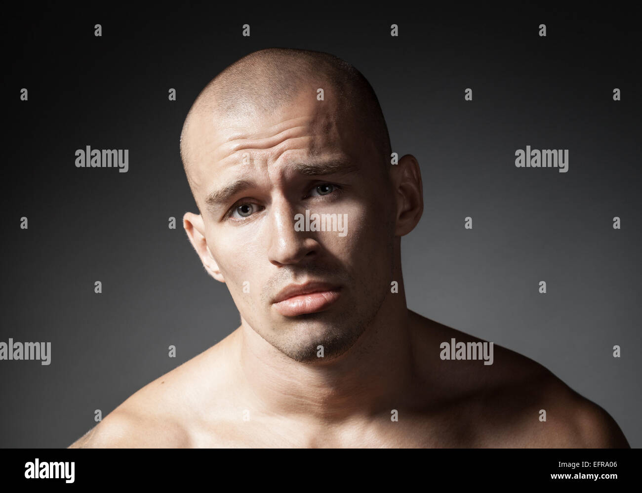 portrait of pitiful strong man isolated on gray background - Stock Image